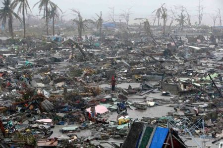 People-stand-among-debris-and-ruins-of-houses-destroyed-after-Super-Typhoon-Haiyan-battered-Tacloban-city-in-central-2718533