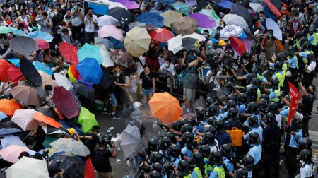 Protesters carrying umbrellas brave pepper spray used by riot police as tens of thousands of demonstrators block the main street to the financial Central district outside the government headquarters in Hong Kong